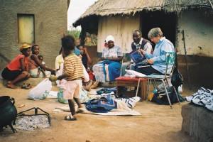 Eni's huis. Ina met dominee Piet Mavheta, Eni's nicht 'Malori' die vertaalt. Eni zit verborgen achter een kleinkind.