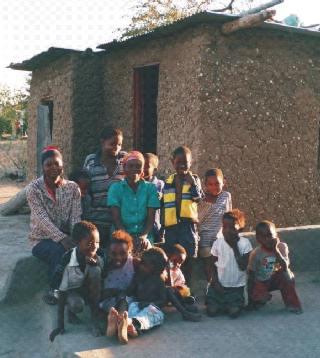 Florah (in het groen) tussen haar kinderen en kleinkinderen, voor het huisje dat ze en haar man gebouwd hebben.