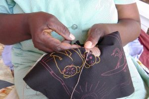 Sani sits quietly and embroiders
